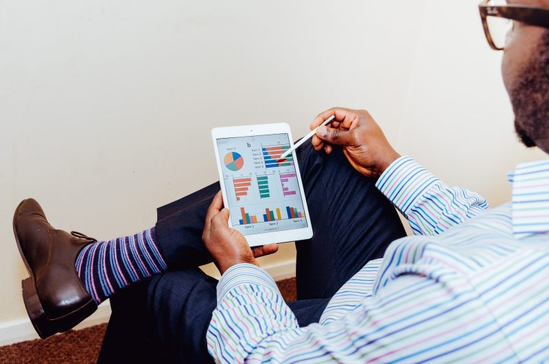 man using a tablet with charts while sitting